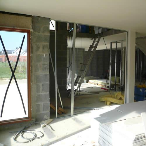 Pose de l'ossature métallique des plaques de plâtre dans une maison en travaux.